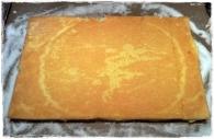 fertigen Biskuit an der kurzen Seite vorsichtig einschneiden und auskühlen lassen